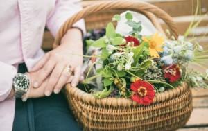 Ein Korb voller Marktware mit einem Strauß bunter Blumen